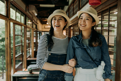 Photo  Laughing group of young asian girlfriends having fun while walking together walkway in japanese style wooden house