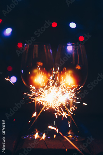 Photo  sparkling Bengal sparklers sticks in flames on a black background with lights bokeh and wine glasses