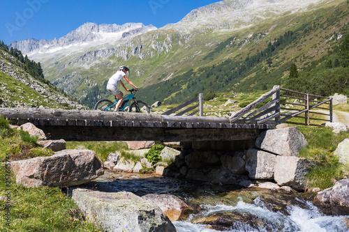 Fotografie, Obraz  Mountainbiking uphill - Female Mountainbiker goes across a wooden bridge in the