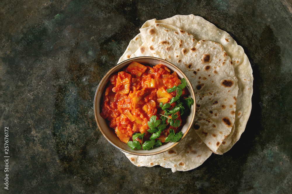 Fototapety, obrazy: Vegan vegetarian curry with ripe yellow jackfruit served in ceramic bowl with coriander and homemade flatbread flapjack over dark metal background. Flat lay, space