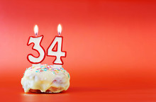Thirty Four Years Birthday. Cupcake With White Burning Candle In The Form Of Number 34. Vivid Red Background With Copy Space
