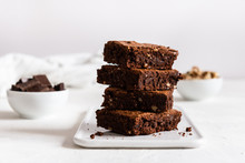 A Stack Of Chocolate Brownies On White Background, Homemade Bakery And Dessert. Bakery, Confectionery Concept. Side View