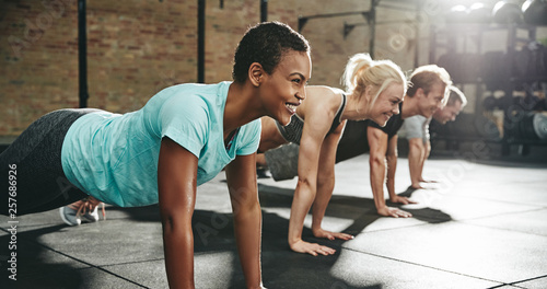 Leinwand Poster Young woman smiling while doing pushups in an exercise class