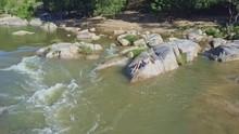 Drone Moves Along Girl Lying On Rock Among Foamy Rapids
