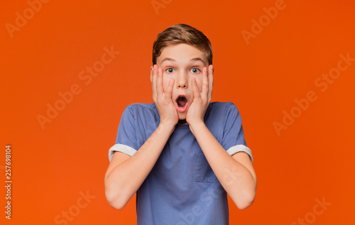 Fotografija  Shocked kid keeping mouth open and touching face