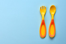 Baby Food Concept Background. Baby Plastic Fork And Spoon, Copy Space.