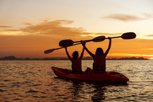 Two Girls Kayaking In The Sea At Sunset