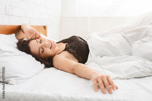Obraz Smiling woman waking up in her bed - fototapety do salonu