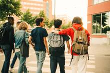 Rear View Of Male Friends Crossing Road Side By Side In City