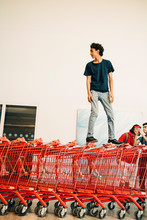 Carefree Teenage Boy Standing On Stacked Red Shopping Carts Outside Mall