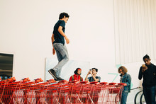 Young Man Photographing Friend Walking On Stacked Shopping Carts Outside Mall