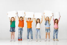 Group Of Happy Smiling Children With A White Empty Banners Isolated In White Studio Background. Education And Advertising Concept