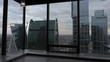 young woman silhouette in long cardigan dances near french windows against modern tall buildings under cloudy sky