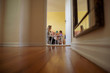 Surface level image of mother with daughter sitting against wall in room seen through doorway at home
