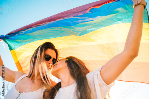 Pinturas sobre lienzo  Couple lesbian woman with gay pride flag on the street