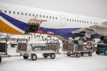 Baggage Loading At Airport In Winter. Luggage In Carts Near Aircraft In Winter. Passenger Aircraft In Winter At Airport Loaded Baggage Before Departure.