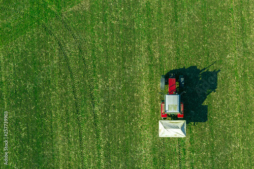 Spoed Fotobehang Groene Agricultural tractor fertilizing wheat crop field with NPK