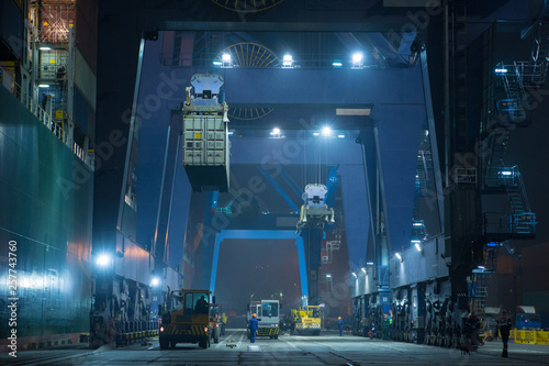 Montage in der Fensternische Shanghai operation of container terminal at night. Unloading container ship at night. Mooring cranes unload container ship at night