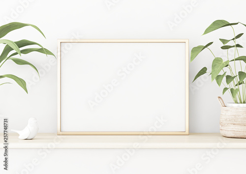 Horizontal poster mockup with golden metal frame standing on wooden table and decorated with green plants in basket on empty white wall background. 3D rendering, illustration.