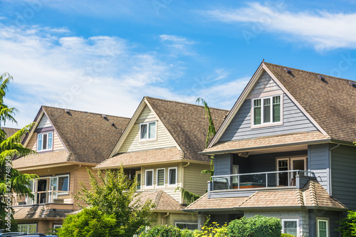 Fotomural Top of three residential houses on blue sky background
