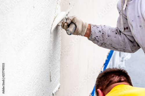 Fotografía  Construction worker plastering and smoothing concrete wall with cement