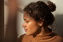 Close-up Of Serious Thoughtful Woman Looking Away While Sitting Against Wall At Home