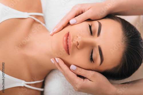 young woman getting a head massage at a spa Wallpaper Mural