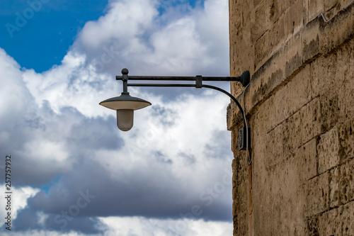 Fotografie, Obraz  Typical street lamp with cloudy summer August sky background over alley in Mater