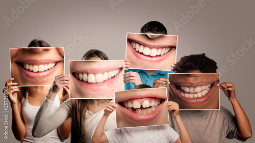 fototapeta na szkło group of happy people holding a picture of a mouth smiling on a gray background