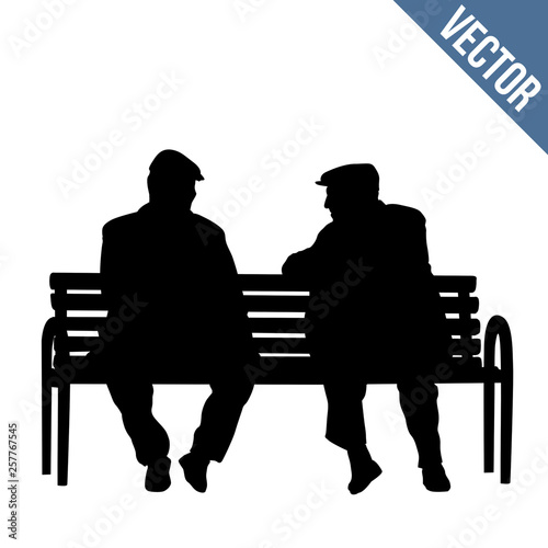 Cuadros en Lienzo Two elderly people silhouettes sitting on a park bench