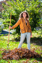 Young Happy Woman Homeowner In Garden Yard Backyard Raking Collecting Of Dry Autumn Foliage Oak Leaves Standing With Rake In Sunny Fall