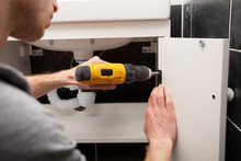 Worker Installing Doors On The Closet. Furniture Repair And Assembly Concept. Young Man Assembling Bathroom Furniture. Hands Close Up.  Carpenter Working With Screwdriver.