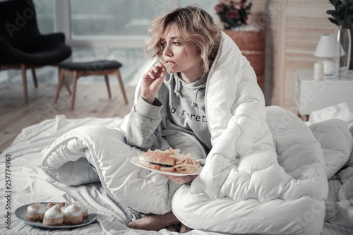 Fototapeta Sad and lonely woman eating burger and French fries in the bed obraz