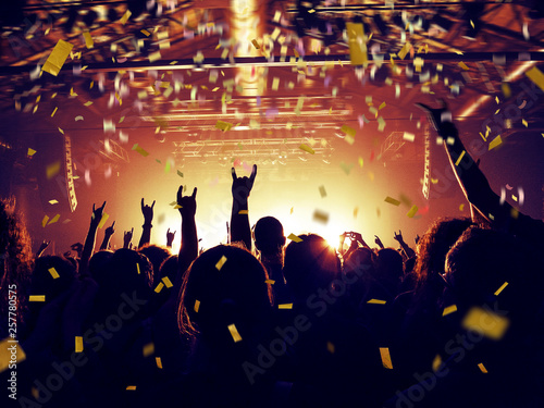 Confetti falling inside a crowded concert hall - 257780575