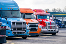 Row Of Different Big Rigs Semi Trucks On Truck Stop Parking Lot Waiting For Continuation Of The Road Routes