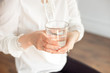 Glass of clean mineral water in woman's hands. Concept of environment protection, healthy drink.