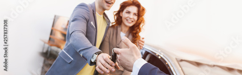 Photo  panoramic shot of car dealer giving keys to cheerful man and woman in car showro