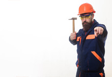 Industrial Worker. Engineer. Builder In Helmet Holds Hammer. Mechanic In Uniform With Hammer Pointing At You. Repair Service. Handyman With Hammer. Construction Worker In Hardhat Pointing To Front.