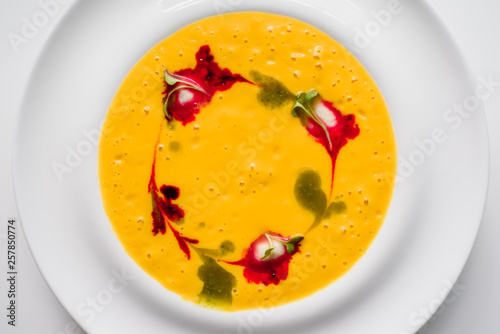 beautifully decorated pumpkin cream soup in a white plate