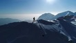 Aerial slow motion - Man hiking on top of snowy mountain at beautiful sunset