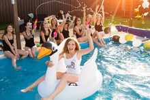 Happy  Beautiful Girlfriends Having A Great Time At The Hen Party. Attractive Young Women Bride Floating On A Big Inflatable Swan In Pool.