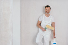 Painter In White Dungarees Holding A Roller