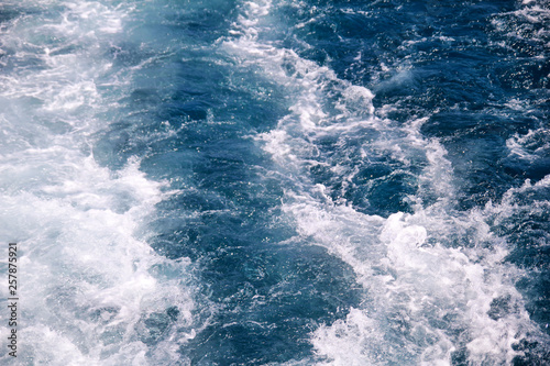 Autocollant pour porte Eau Turbulence made by foam of sea water from a high-speed yacht on surface of sea. Blue sea waves with lot of sea foam. Surface of sea with waves, splash, foam and bubbles, blue background and wallpaper.