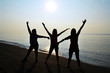 Silhouette of 3 ladies with sunrise on the beach