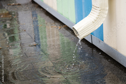 Photo  White drainpipe with flooded pavement
