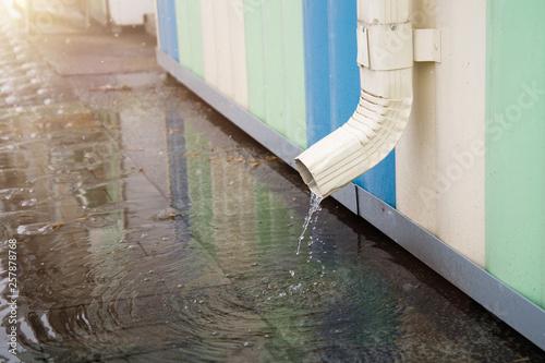 Valokuva  White drainpipe with flooded pavement