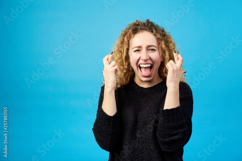Fotografía Emotional satisfied young attractive redhead curly woman with opened mouth crossing fingers for good luck