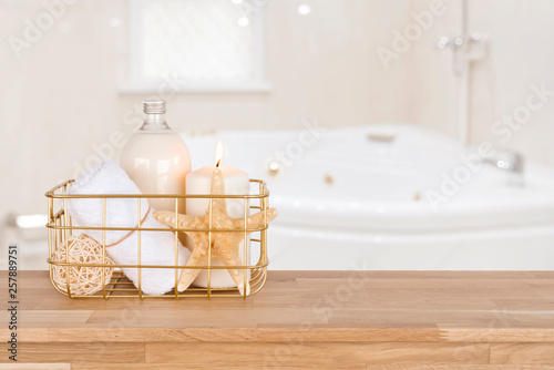 Photo sur Toile Spa Spa products in basket on wood table over blurred bathtub