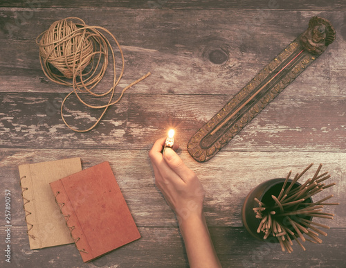 Woman hand lights a incense stick from a Buddha holder on a