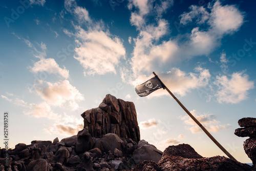 Obraz na plátně coastal landscape of rocks with pirate flag